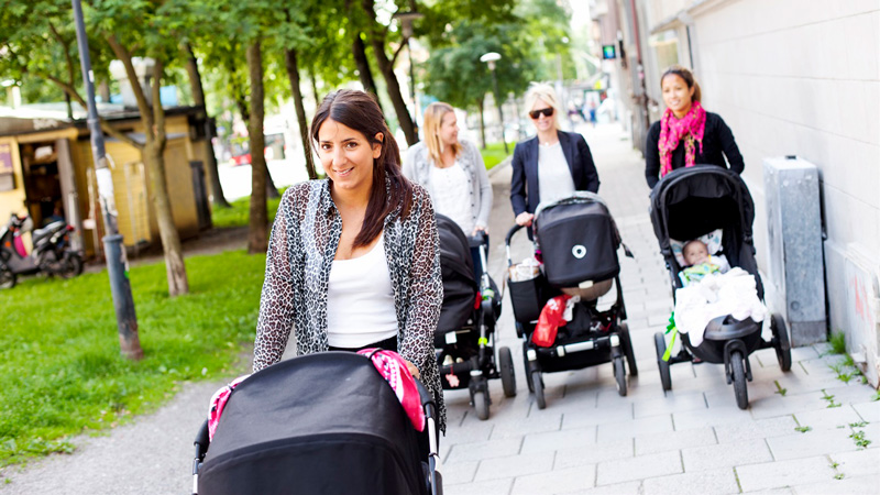 Mammor på promenad med barnvagnar