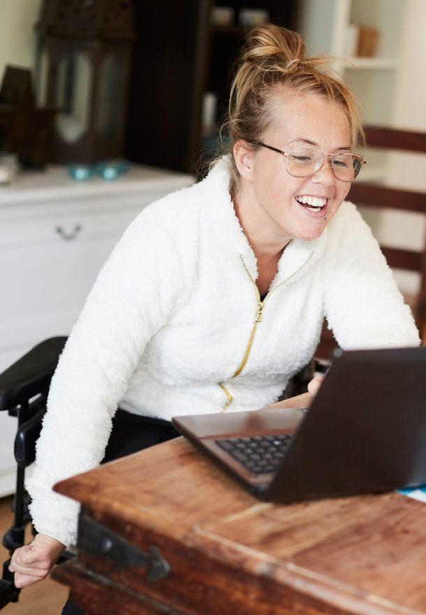 Kvinna använder laptop i kök hemma