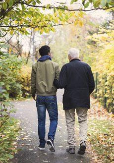 En ung och en gammal man håller armkrok på promenad.