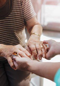 Äldre och yngre kvinna som håller händer.